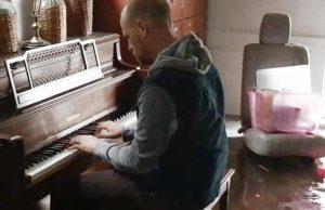 Pai se apoia ao piano após perder a casa em furacão